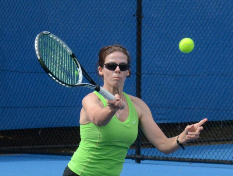 A female tennis player lines up for a shot