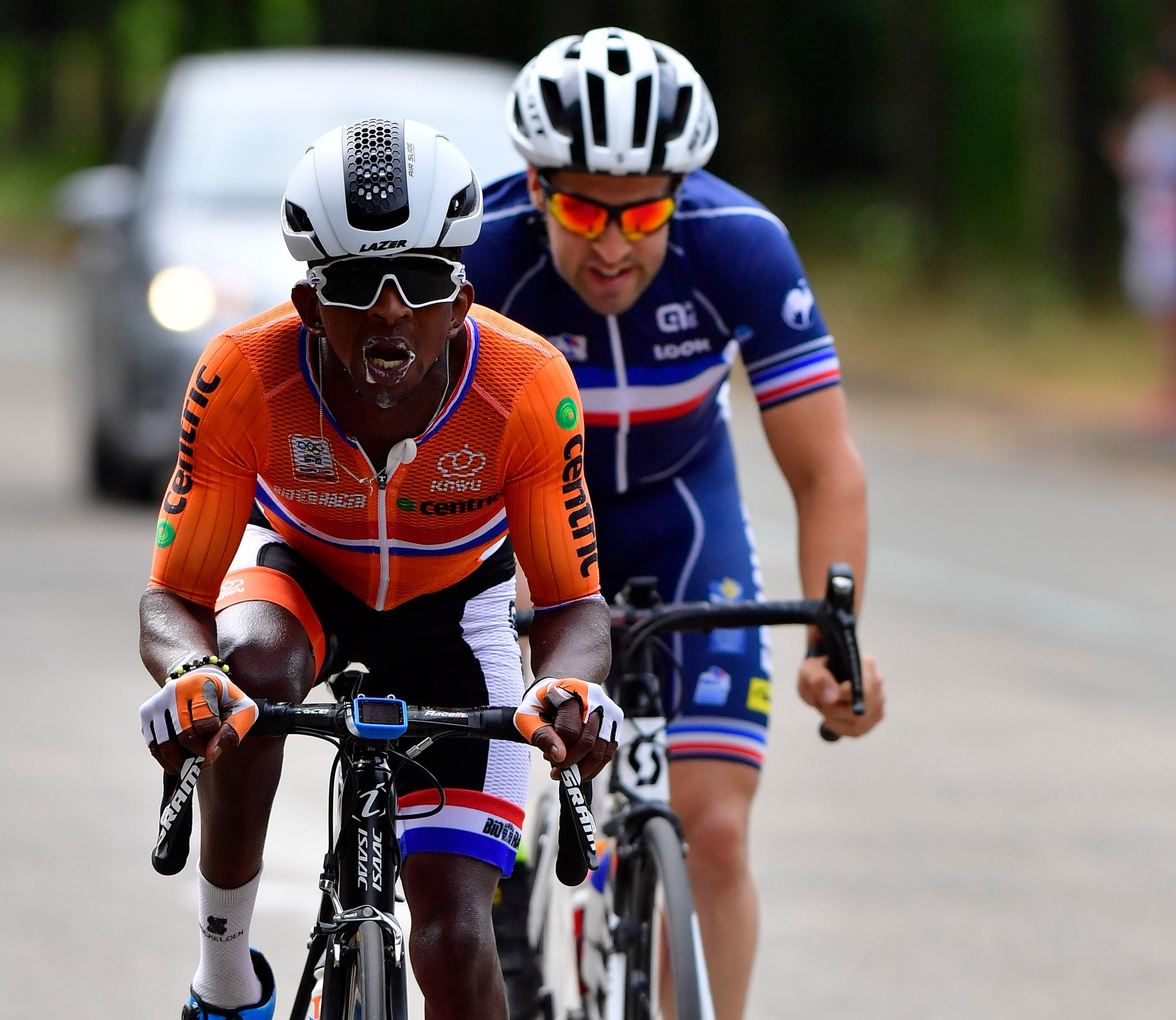 Two cyclists are pictured during a race, making a huge amount of effort.