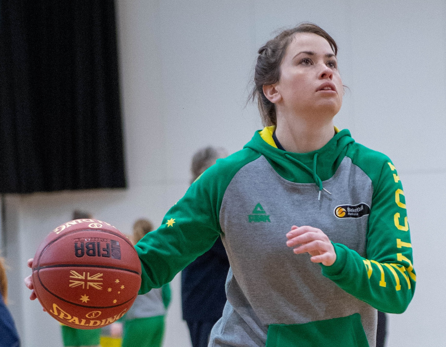 A female basketball player is pictured during practice, looking towards the net whilst holding a basketball in her hand