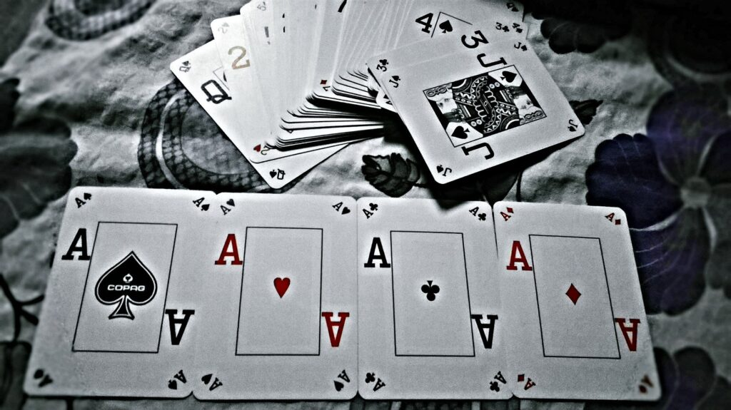 Shows a strong poker hand, 4 aces.