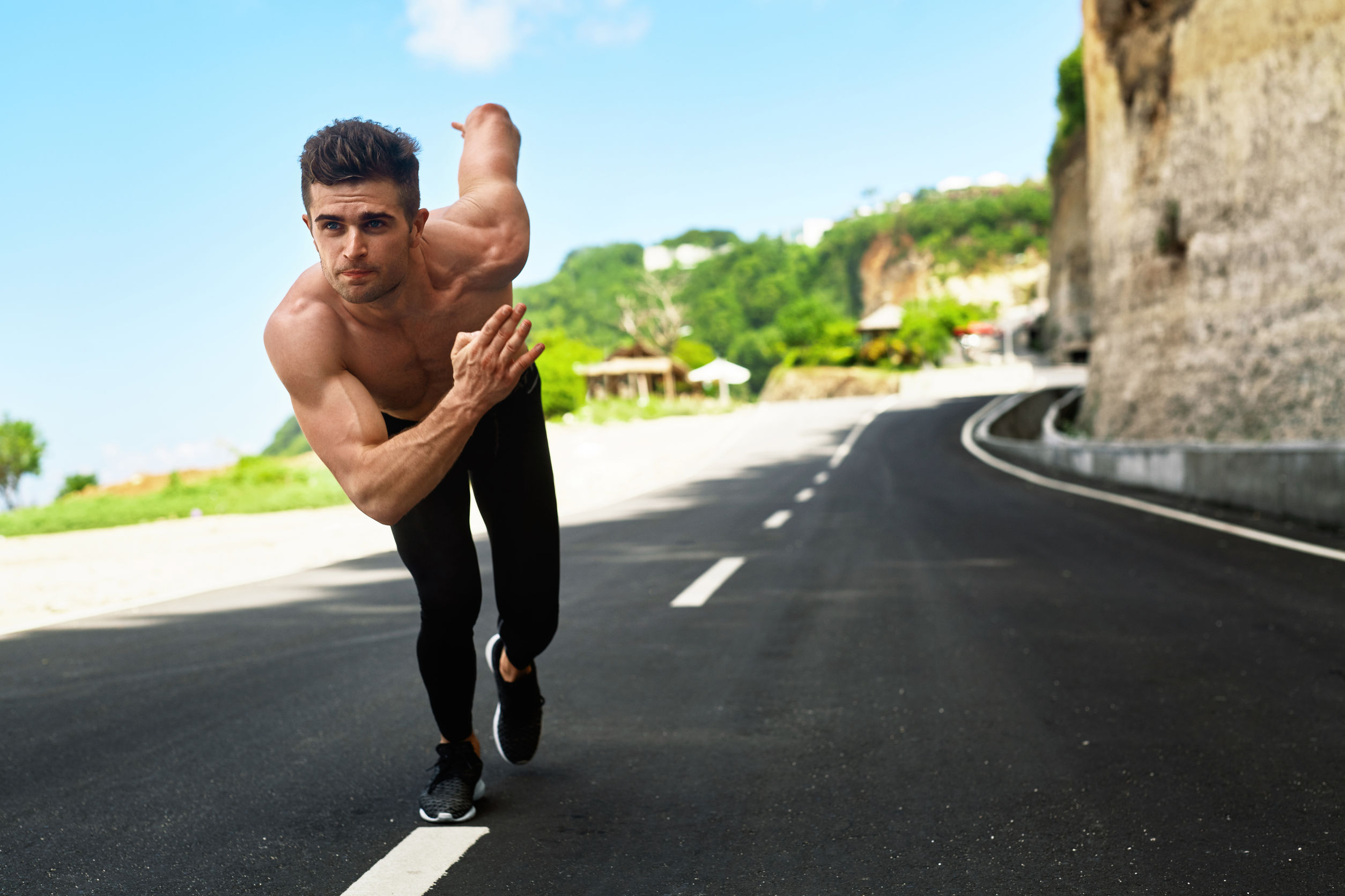 57159660 - athletics. athletic man with fit muscular body in starting position for running on road. handsome runner ready to start sprint race. fitness model training outdoors in summer. sports workout concept