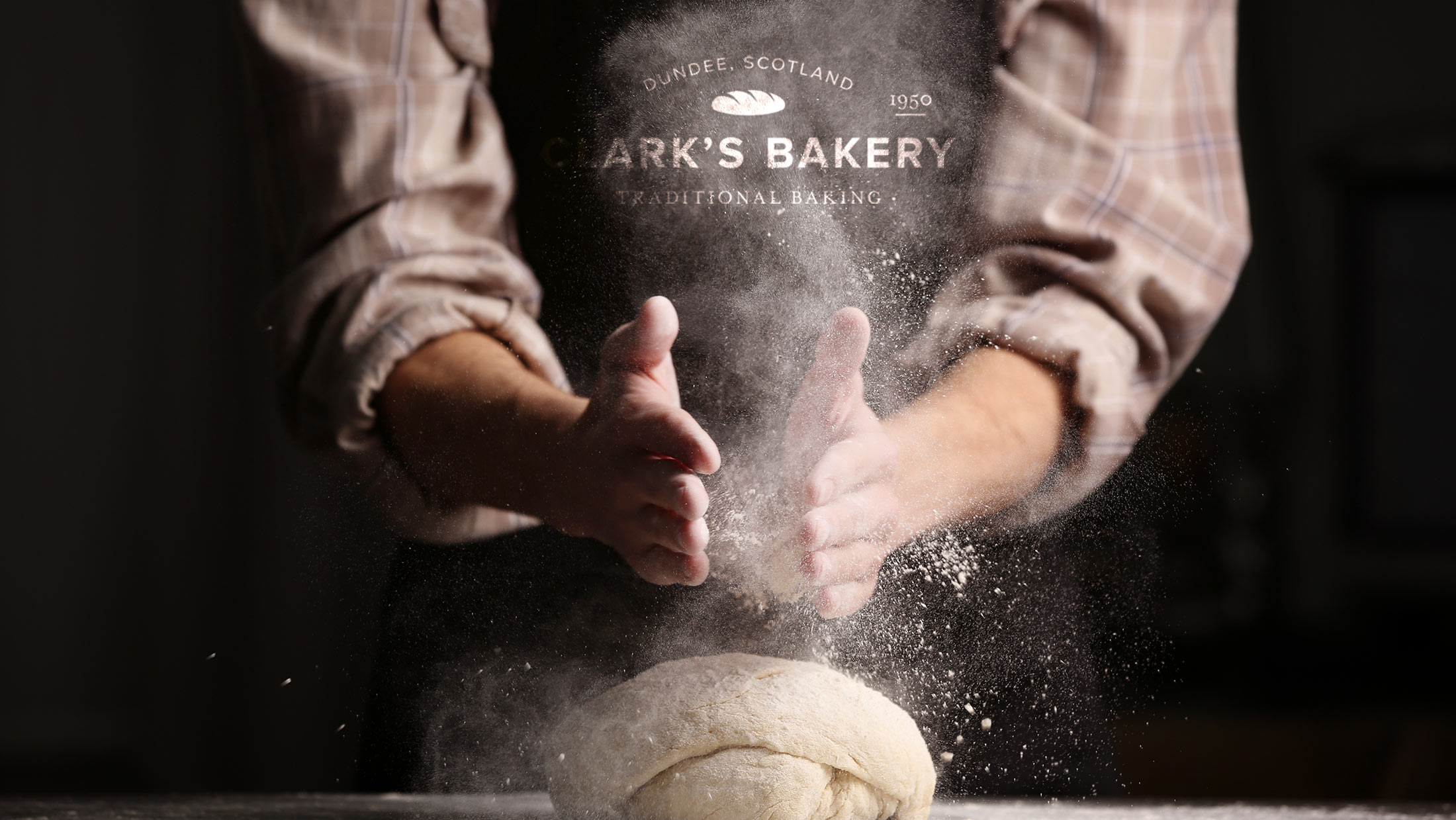 Baker kneading bread dough wearing a black apron with the Clark's Bakery logo on the front