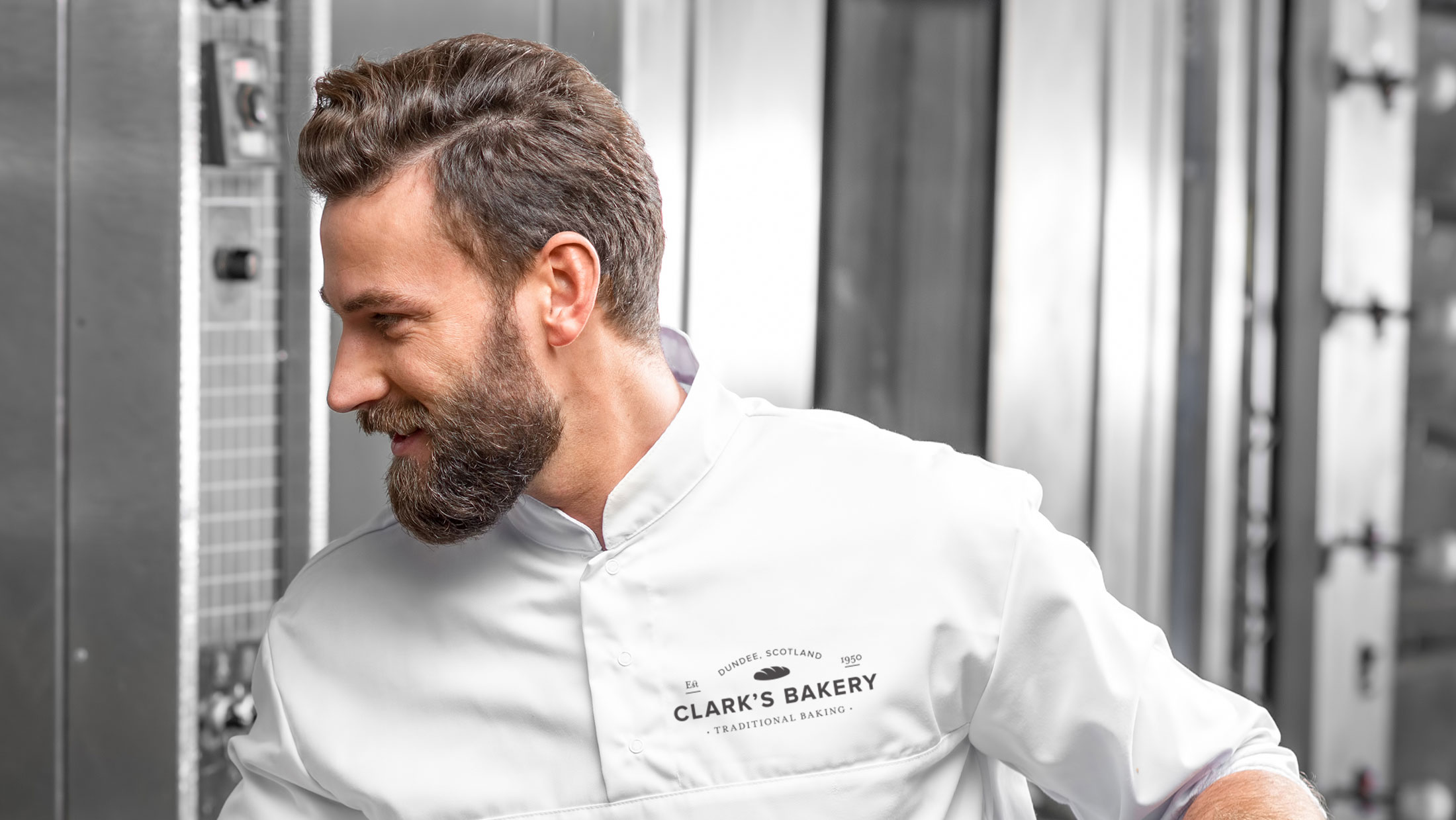 Man with beard wearing baker's whites with the Clark's Bakery logo