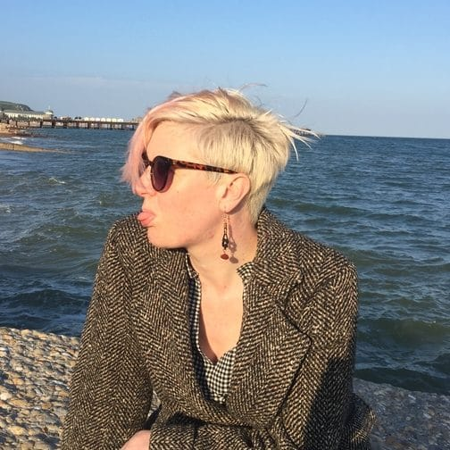 Photo of a non-binary person with short bleached blonde hair sitting on a concrete beach groyne wearing a tweed coat. They are looking towards the viewer's left and their tongue is stuck out. They are wearing sunglasses. The sea and blue sky are in the background.