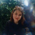 Jennifer, a white woman in her 30s, is sat at a table tilting her head and smiling at the camera. She has shoulder-length brown hair, is wearing red lipstick, a black jumper, and tortoiseshell sunglasses rest on top of her head. She is holding a phone in her hands and her nails are painted red.