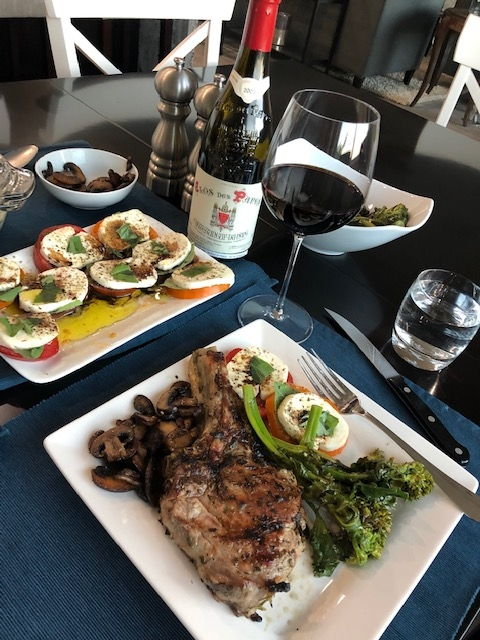 Grilled veal chop with rapini and caprese salad