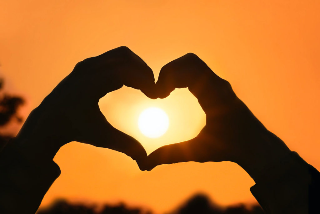 heart made with hands towards the sun