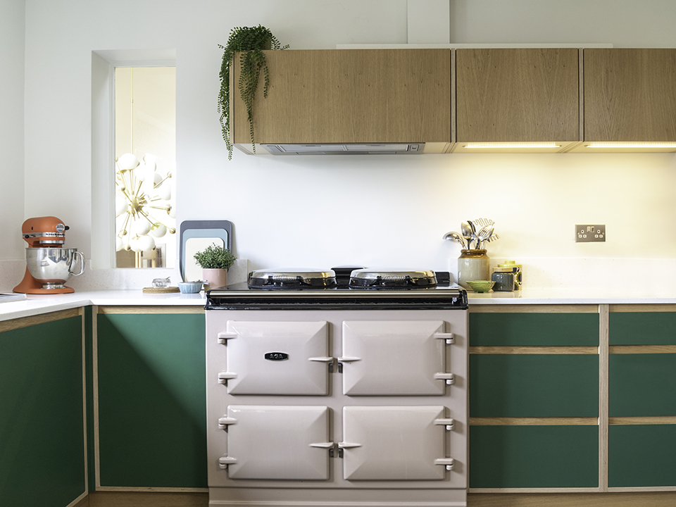Custom kitchen with green cabinets and pink aga
