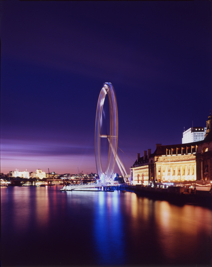 From Westminster Bridge at dusk in mid-summer, with blue light on capsules. The London Eye by Marks Barfield Architects