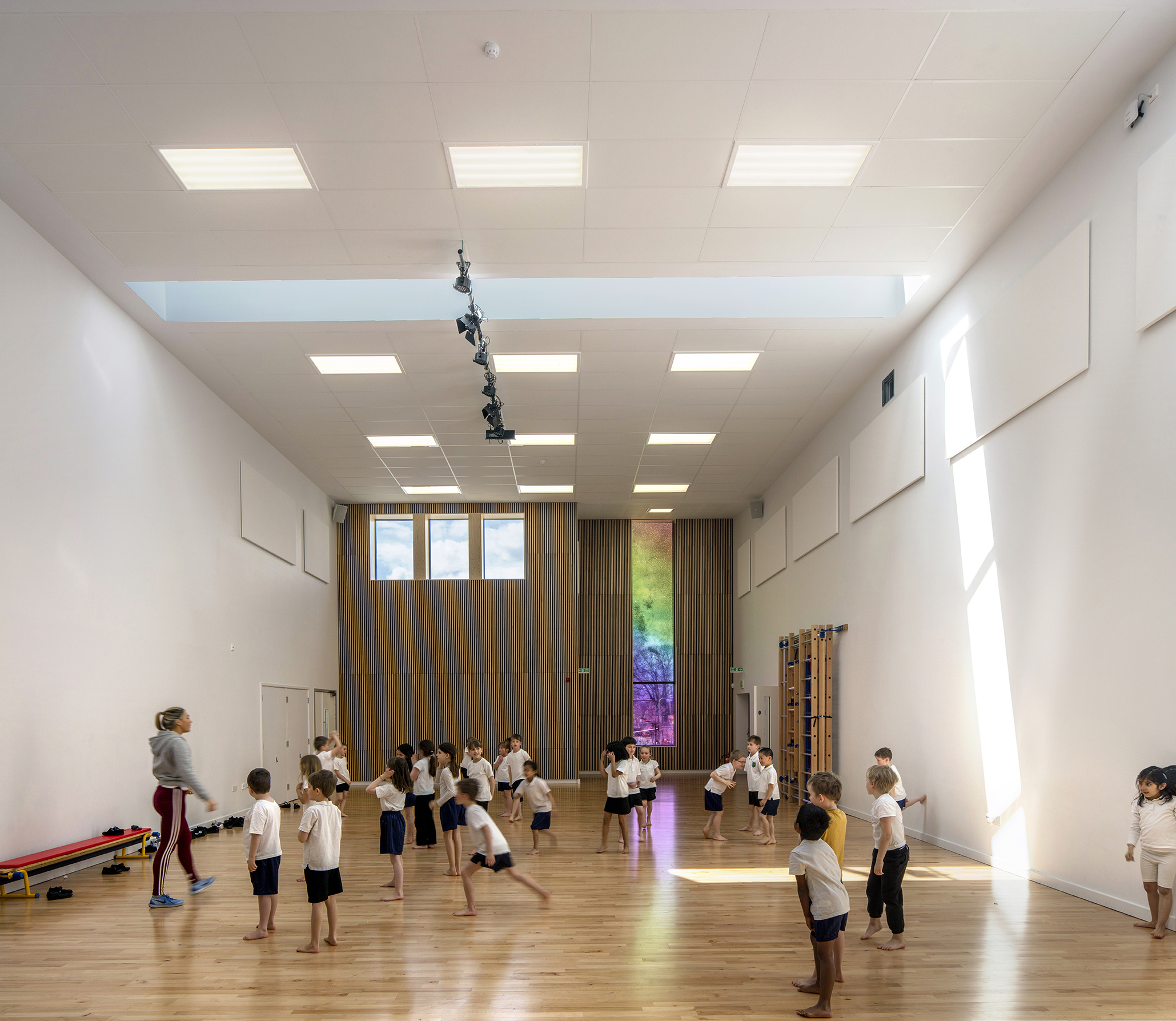 kids exercising indoors - University of Cambridge Primary School by Marks Barfield Architects