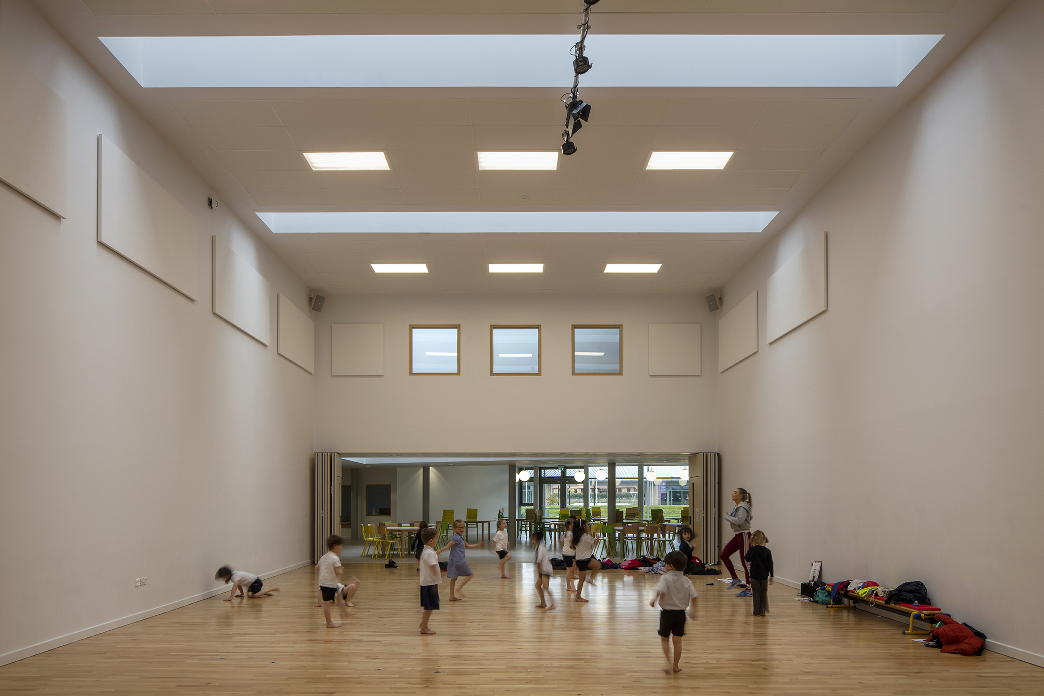 kids exercising interior view - University of Cambridge Primary School by Marks Barfield Architects