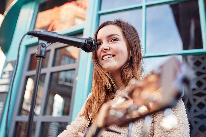 female-musician-busking-playing-acoustic-guitar-QGPZ2UP.jpg