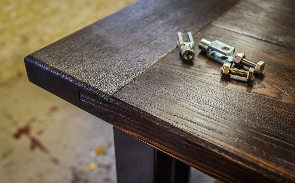 A dark wood top on a vintage industrial style table with nuts and bolts to show manufacturing with a wide metal leg.
