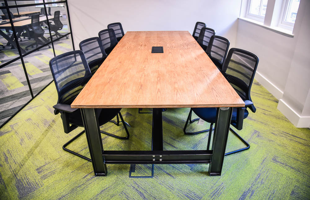 Lancaster - a Spitfire Furniture product as a vintage industrial tables - used as a board room table in a meeting room with green and grey carpet. Wood tabletop and steel legs and black chairs