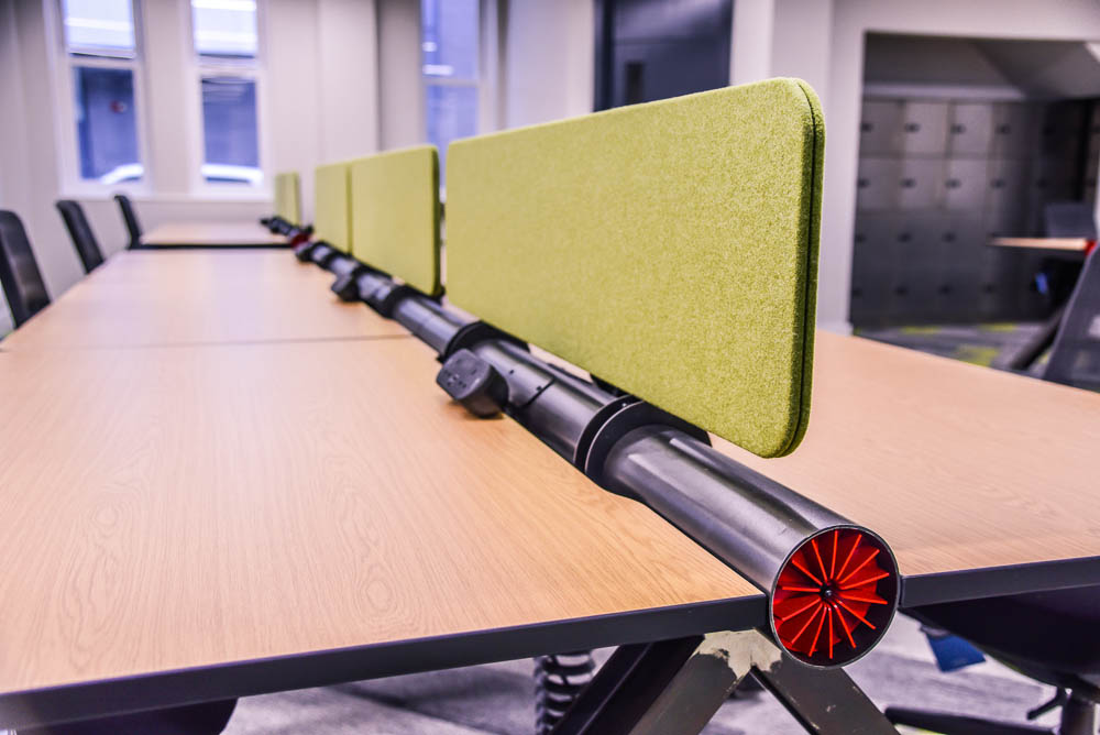 A red turbine on a desk with steel grey legs and a wood desktop - a Spitfire Furniture vintage industrial style desks with green screening between desks