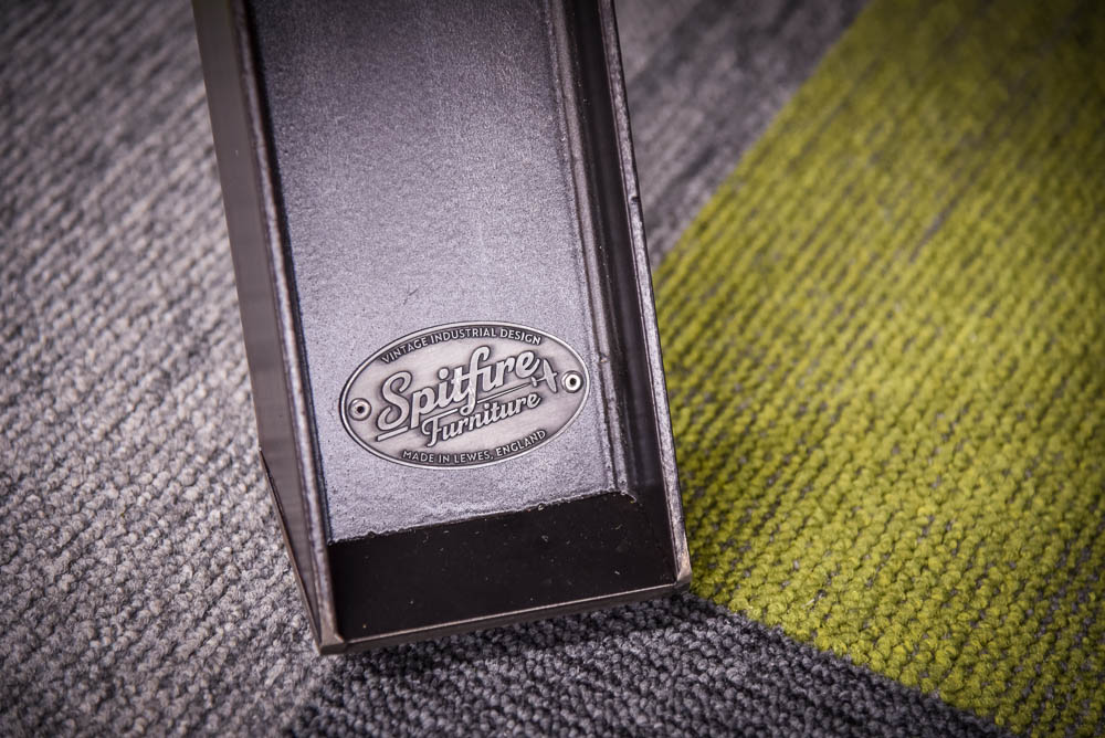 Steel leg of a Spitfire table stamped with Spitfire Furniture logo badge