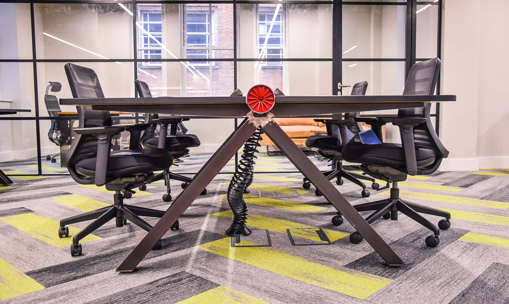 A red turbine on a desk with steel grey legs and a wood desktop - a Spitfire Furniture vintage industrial style desks with chairs in an office with green and grey carpet