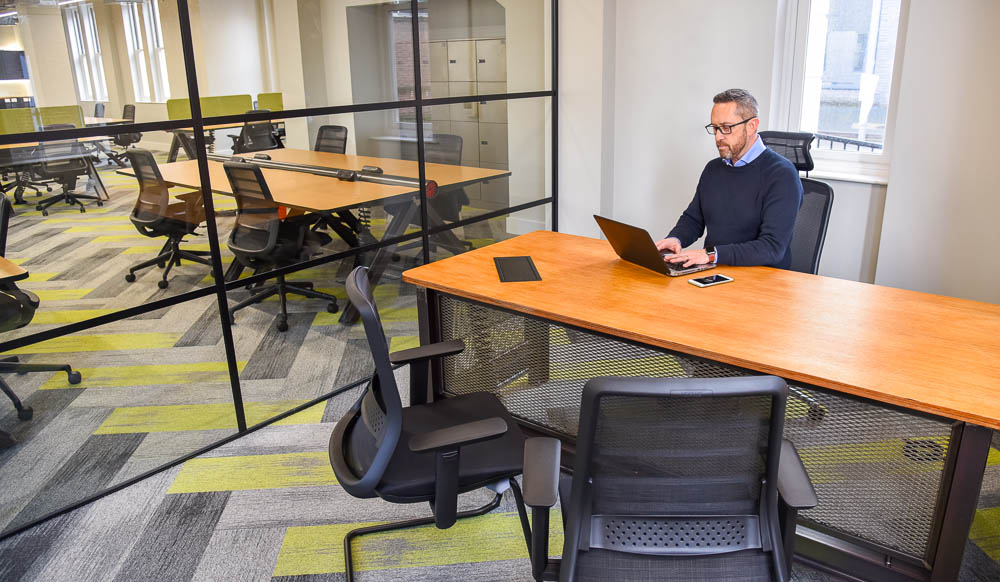 Office furniture suppliers supply office furniture for a modern office with vintage industrial theme. man sits at desk in meeting room, at wooden office table with metal steel mesh and chairs with laptop. Windows out to office.