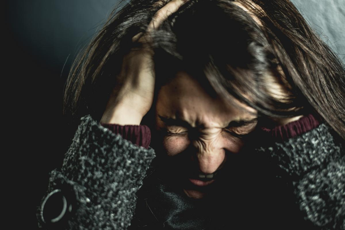 Brunette woman screaming from head pain, anxiety, brain injury