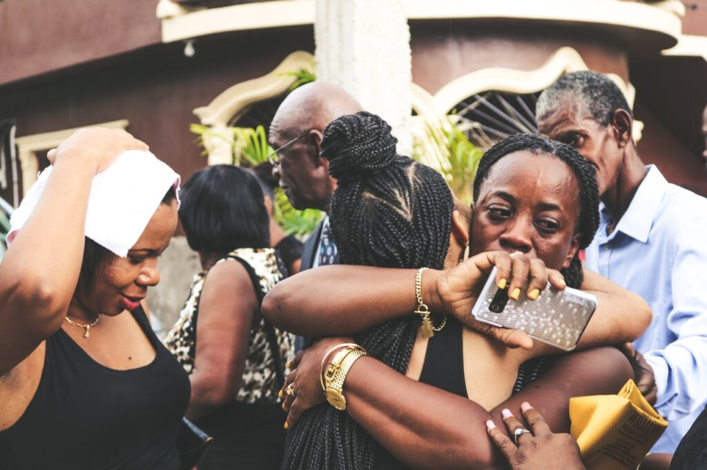 Upset black woman hugging another black woman