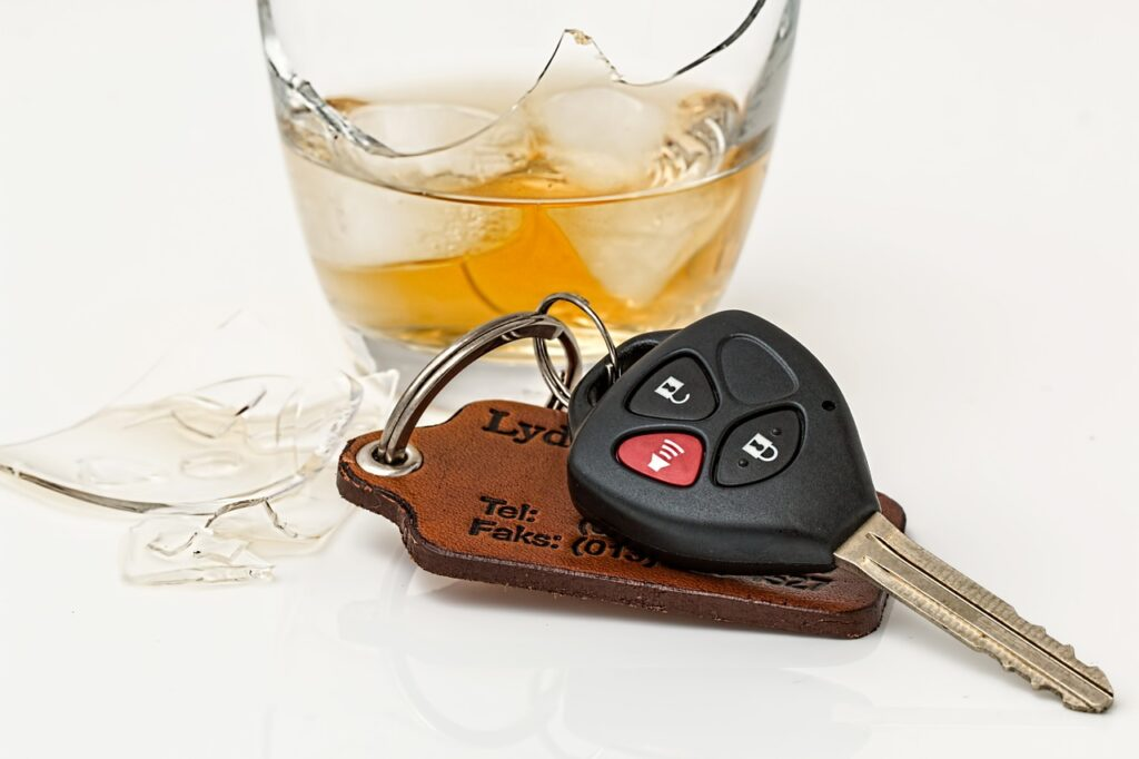 Alcoholic drink in broken glass and car keys