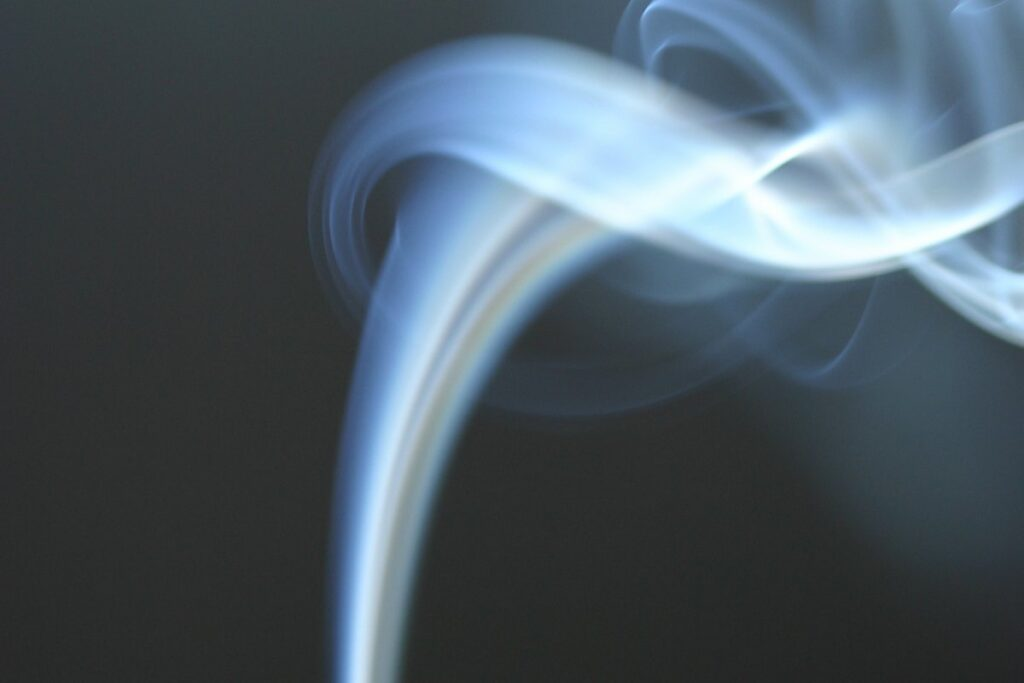 Fumes of gas flowing up on a black background