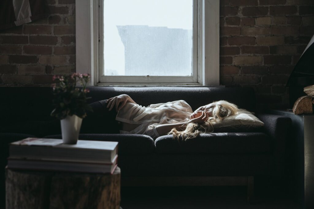 Woman laying on a couch, feeling ill