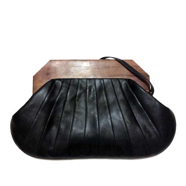 Origami clutch in black leather. Teak wood handle and leather strap. Exterior design has a folded leather look.
