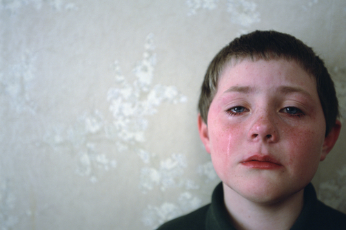 A young boy's tear streaked face is red from crying.