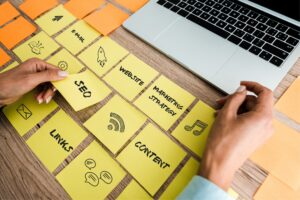 cropped view of woman touching sticky note with seo lettering near laptop on desk