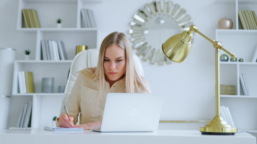 Young girl writing in notebook at work table