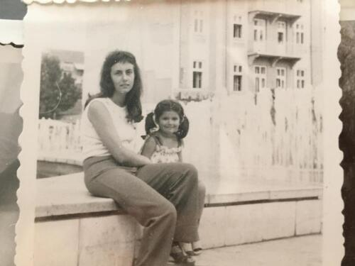 Emanuela with her mother in front of typically socialis-building