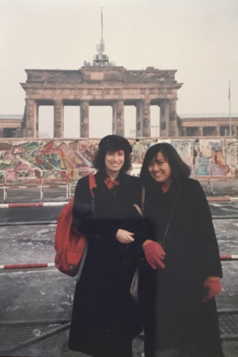 "Susie and her American friend, Gina Borromeo, in front of Brandenburg Gate 11.30.89. Notein all these photos, I am wearing my ""uniform"" in which I travelled throughout the GDR even illegally"