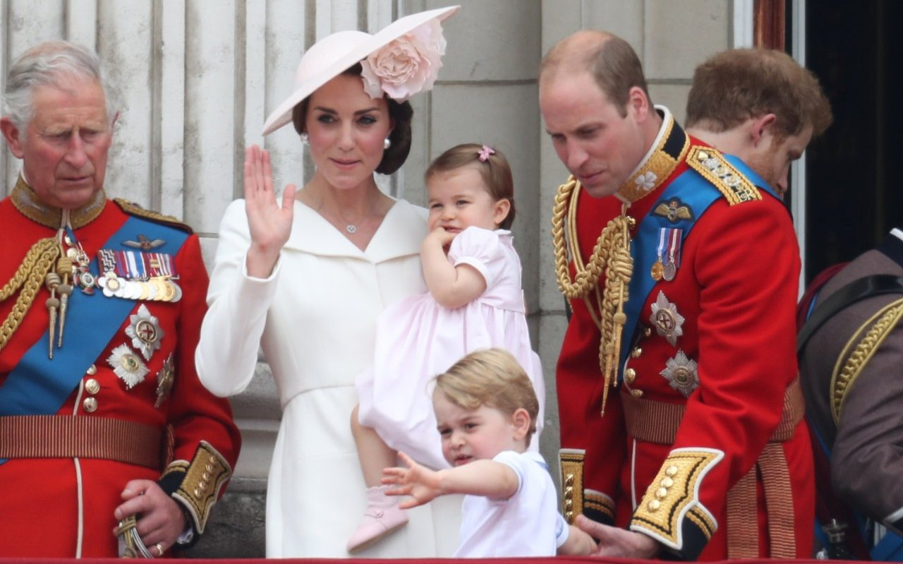 Carried by her mother the Duchess of Cambridge, Princess Charlotte is dressed in a pale pink dress with a pink bow clip in her hair