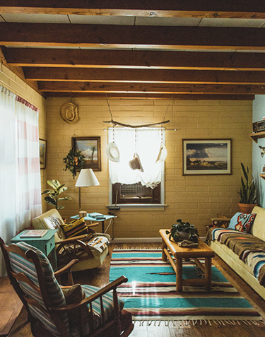 A rustic home with southwestern style decor, warm lighting, and exposed wooden beams.
