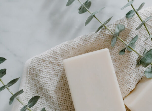 a white piece of soap on top of a white, waffle-patterned wash cloth and a piece of eucalyptus on a white table