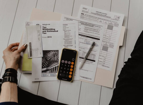 Birdseye image of a person working through tax statements on the floor, with an iPhone calculator and a pen.