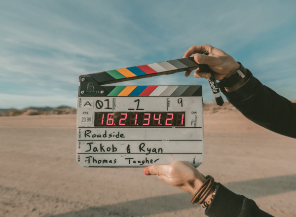 Person holding a clapperboard with a roadside at the background.