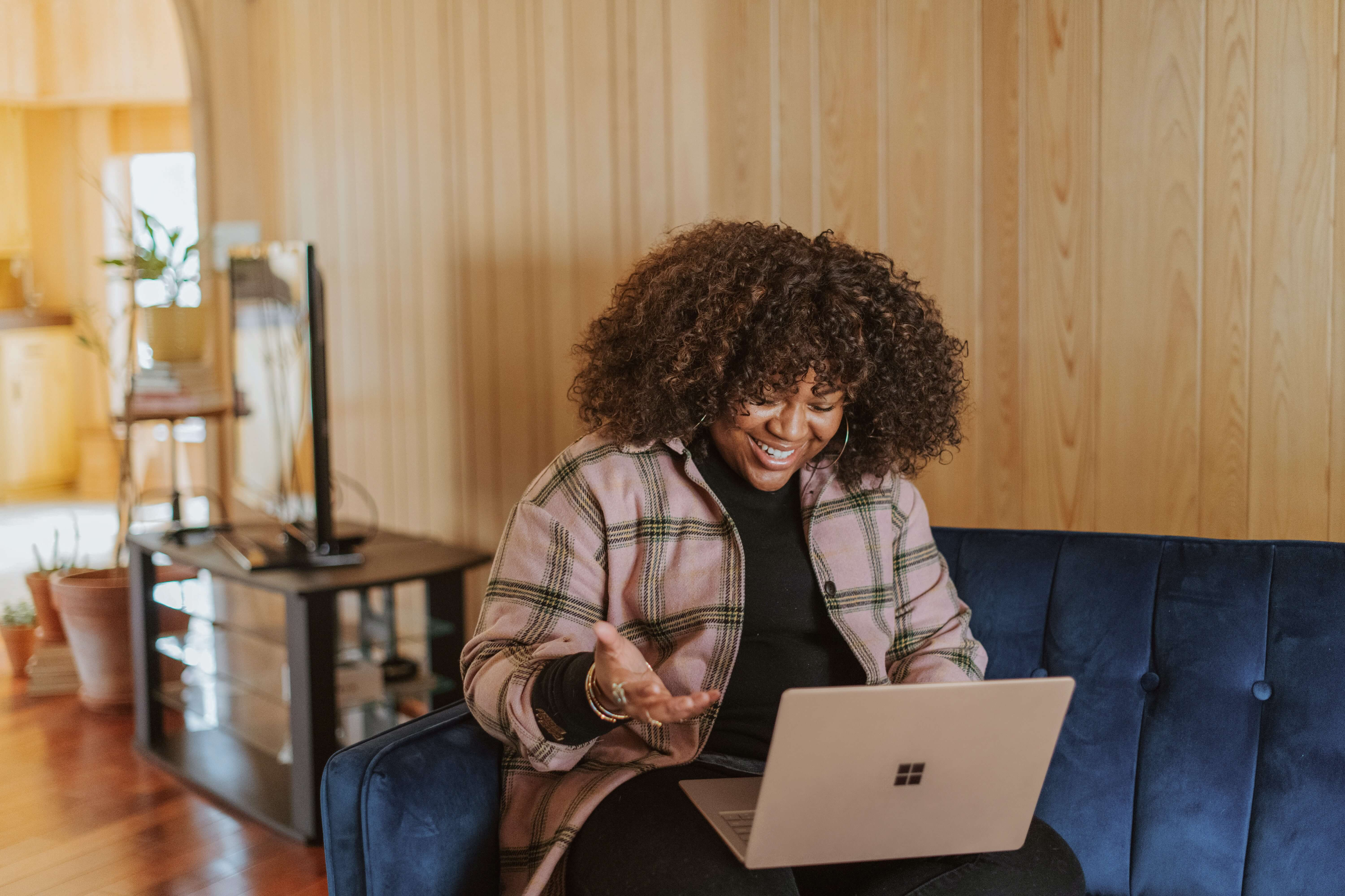 Woman sitting down on a blue sofa, smiling and looking at her laptop.