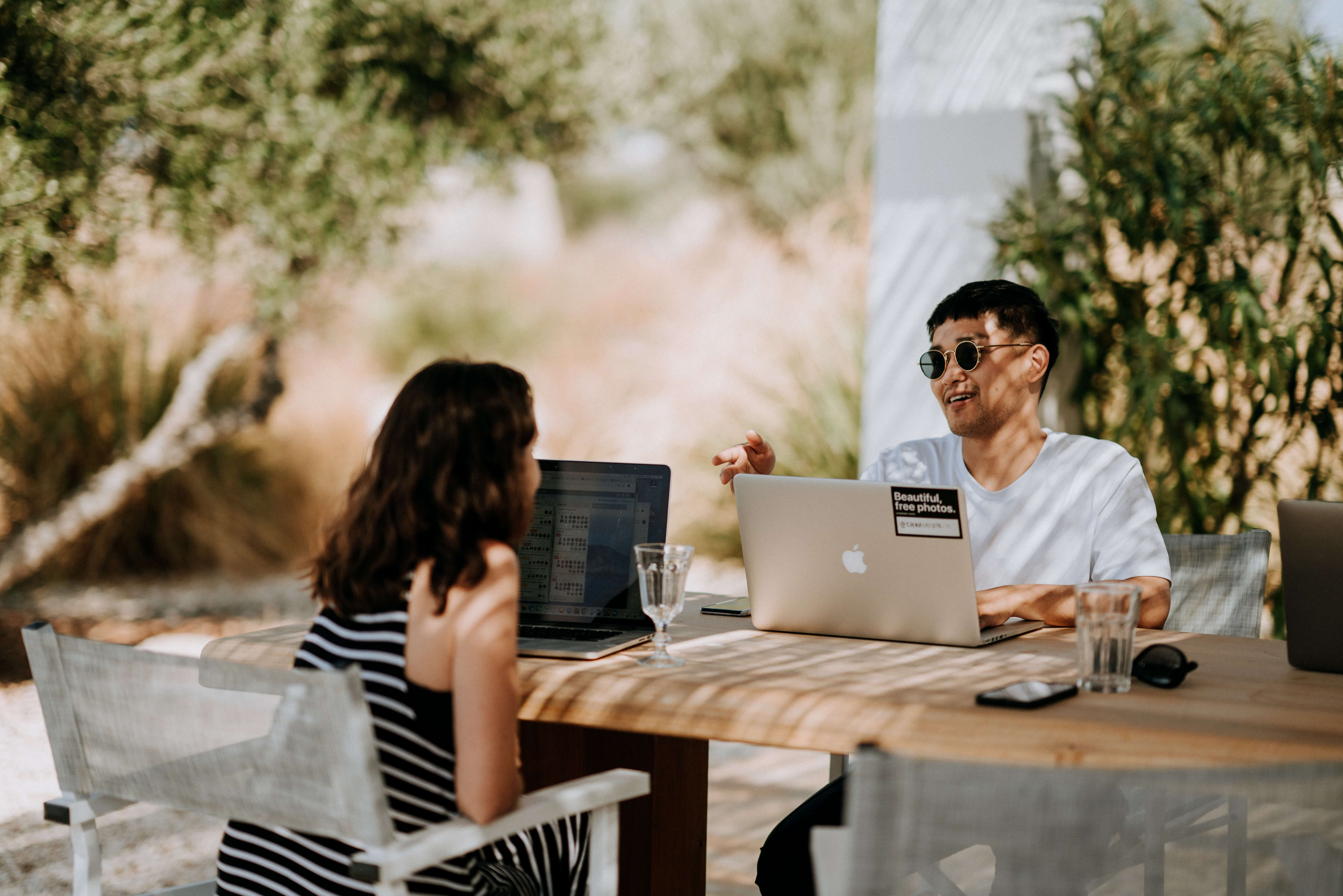 A man and a woman sitting outside and their laptops are on the table.