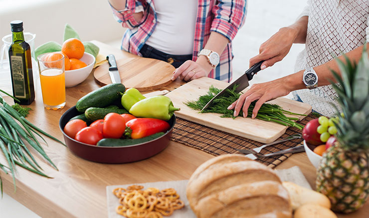 Two persons cutting vegetables on a cutting board