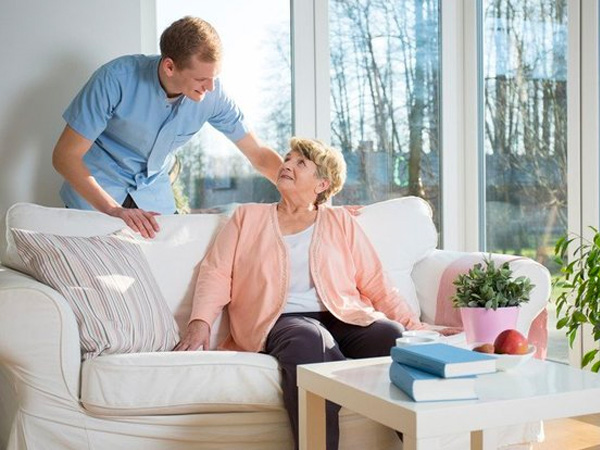 Elderly woman on a couch smiling to its partner
