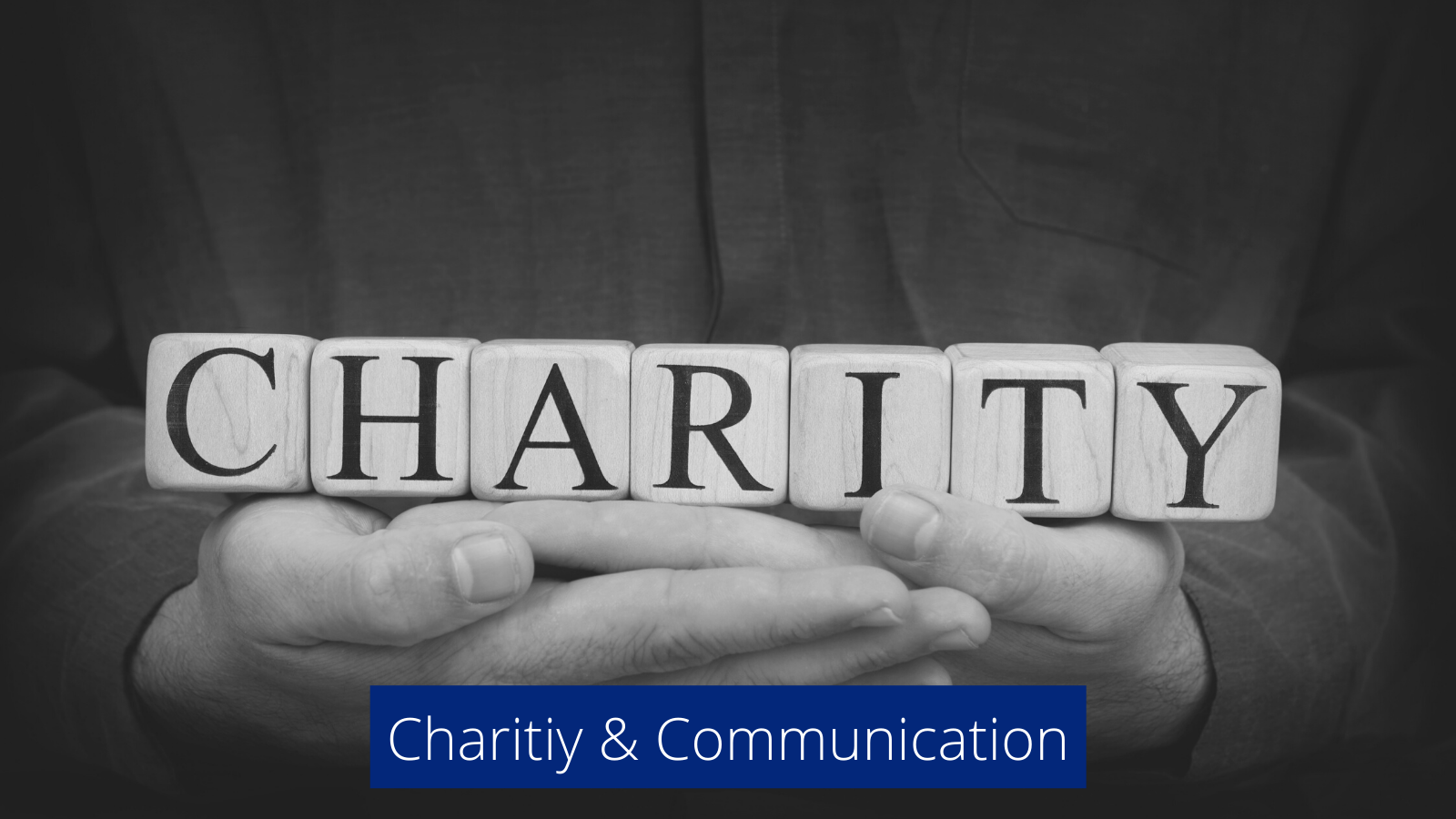 Person holding scrabble letters that spell the word Charity