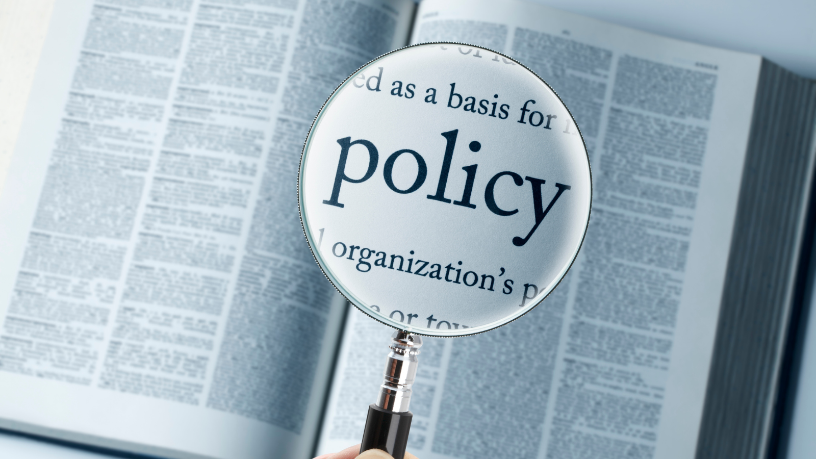 Magnifying glass over a book with the word policy