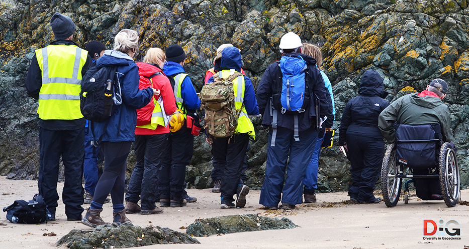 A diverse group of students including a wheelchair user looking at an outcrop of pillow lava in Anglesey, Wales, UK.