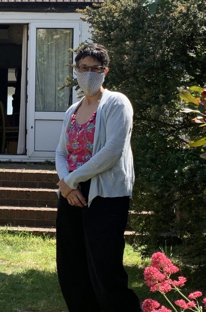 Katie wearing a fabric mask, standing in a garden