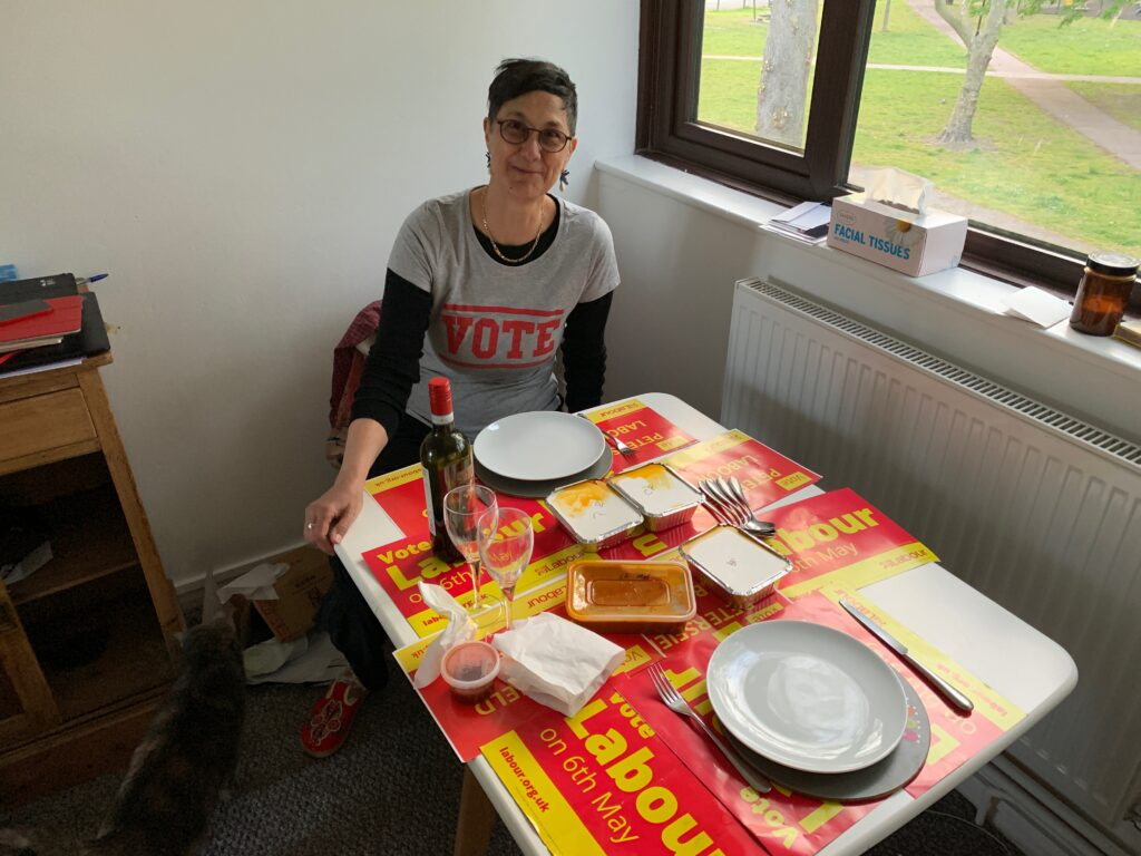 Katie at a table set for a meal, with several Labour posters as table mats