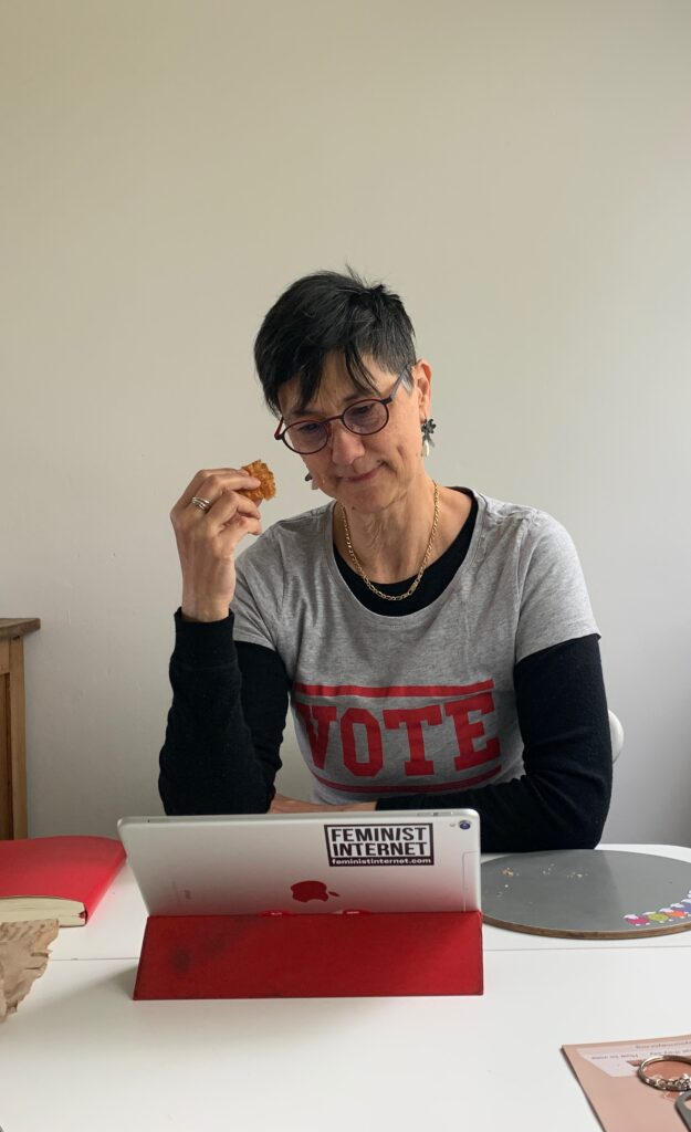 Katie sitting at her iPad, reading emails. She is wearing a 'VOTE' t-shirt