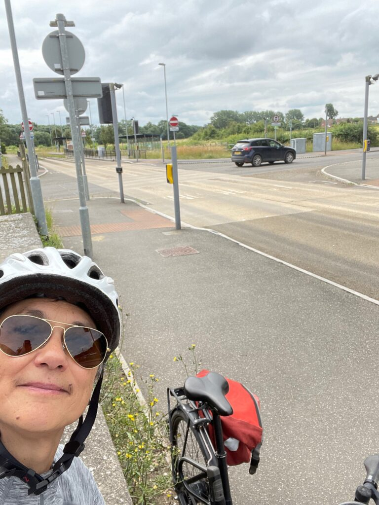 Katie in a cycle helmet, with the guided busway visible