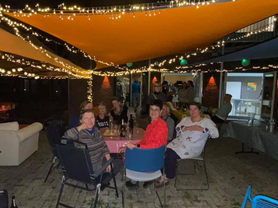 A group of people sitting at a table outdoors with an awning and lights. Katie is at the centre, in a red dress